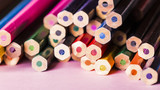 Set of colored pencils for drawing on a pink background.