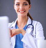 Female doctor working sitting on gray  background