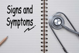 Stethoscope on notebook and pencil with signs and symptoms words
