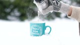 Close up of hand in glove pouring hot tea from thermos into cup on snow. Slowly