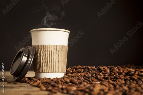 Paper cup of coffee on black background