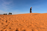Tourist in red sand dunes