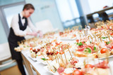Catering. Restaurant waitress serving table with food - 129417819