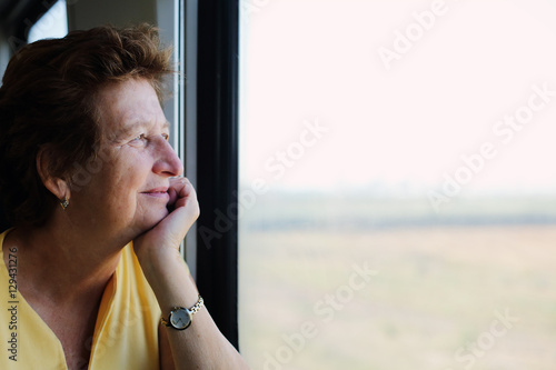 Poster Portrait of beautiful 70 years old woman sitting in the train