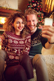 Couple photographing Christmas selfie together