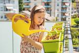 Little girl watering plants on the balcony