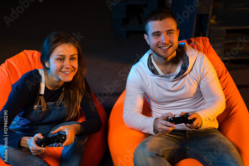 Poster Two young gamer sitting on poufs and playing video games togethe