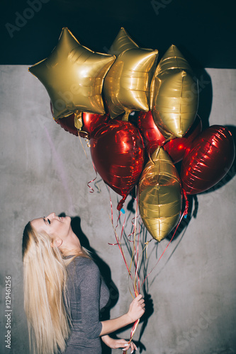 Poster Young woman with gold and red balloons