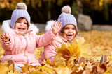 Twin sisters in a park autumn with yellow leaves laughing and having fun happy