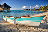 Boat on Bora Bora beach with blue ocean, bungalows background - 129486209