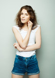 lifestyle, fashion and people concept: young curly woman posing in studio