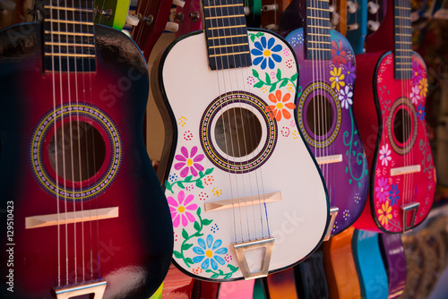 Display of ornate, small Mexican made guitars - 129510423
