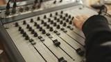 Hands on radio audio mixer sound console.