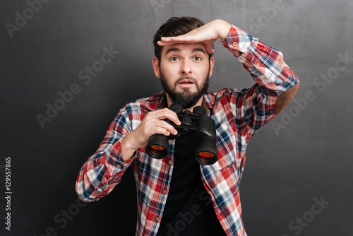Poster Man in plaid shirt holding binoculars and looking far away