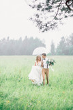 The bride and groom walk with an umbrella. The bride and groom caught in the rain.