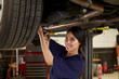 Portrait Of Female Auto Mechanic Working Underneath Car