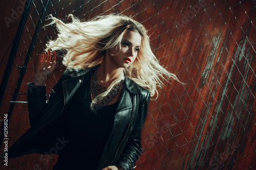 Rock'n'roll girl, young beautiful woman dances in dark alley, against the fence  Poster