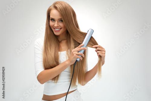 Poster Straight Hair. Beautiful Woman Ironing Long Blonde Hair