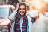 Fototapety Happy young adult woman smiling with teeth smile outdoors and walking on city street at sunset time weating winter clothes and knitted scarf.