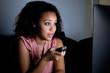 Young woman watching television at night
