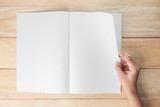 hand open blank book or magazines, book mock up on wood background - 129651082