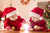 Christmas time. Cute baby twin sisters play with glass balls.