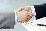 Closeup of handshake with office table and resume background