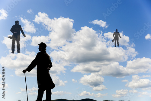 Surrealistic image of silhouettes of men with a cane and bowl hat climbing up th Poster