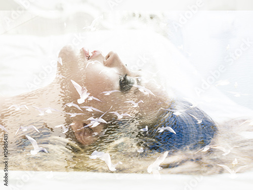 Double exposure of woman lying in bed and seagulls flying - 129685431