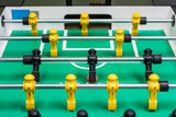 Closeup of foosball table with figures and ball rolling