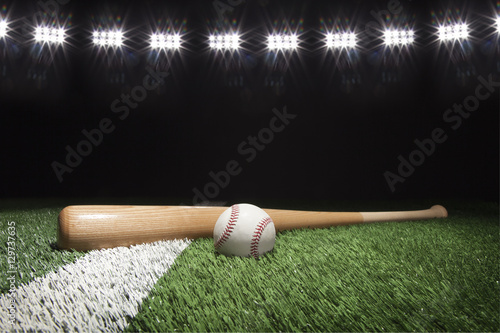 Baseball and bat at night under stadium lights on grass field Poster
