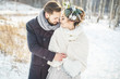 The groom embraces the bride. Beautiful young couple in a Park in winter.