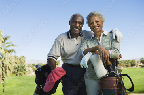 Poster Portrait of happy senior couple in golf course smiling