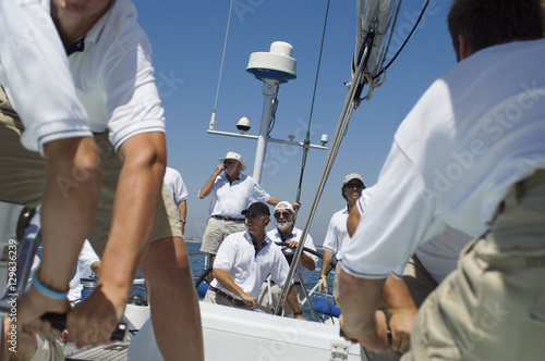 Poster Portrait of a smiling sailor with crew on the sailboat deck against clear sky
