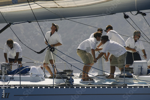 Side view of crew members working on sailboat Poster