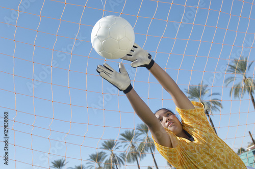 Poster Young female soccer goalie diving to block a goal attempt