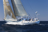 Side view of a group of crew members sitting on the side of a sailboat in the ocean against sky - 129838470