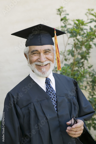 Portrait of a happy male senior graduate smiling outside Poster