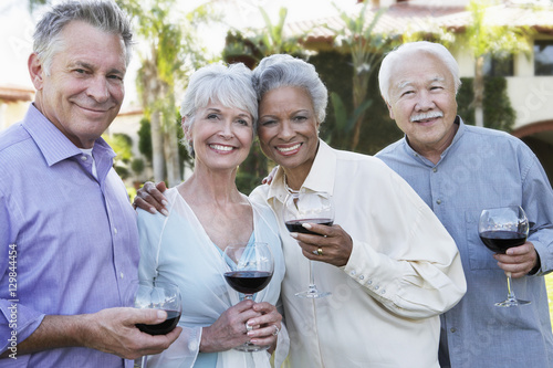 Portrait of happy senior couples standing outside with wine glasses Poster