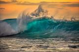 Green blue ocean splashing wave in front of orange sunset sky background - 129901003