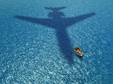 People in a boat under a flying plane