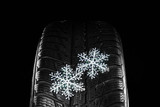 Rubber winter tire with snowflakes on dark background, closeup
