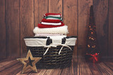 Red, white and green knit Christmas clothes in a wicker basket with Christmas tree - 129962666