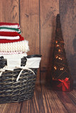 Red, white and green knit Christmas clothes in a wicker basket with Christmas tree - 129962853