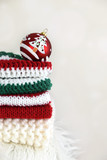 A pile of folded handmade crochet and knit clothes with a Christmas ball - 129963052