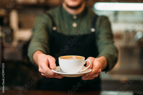 Waiter in black apron stretches a cup of coffee