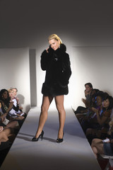 Portrait of a beautiful Caucasian woman in short black furcoat posing on ramp during a fashion show