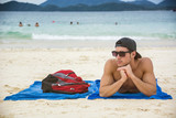 Portrait of a man in a cap and sunglasses sunbathing at Phuket, Thailand