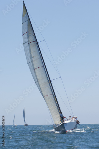 Fototapeta Overview of sailboats racing in the blue and calm ocean against sky