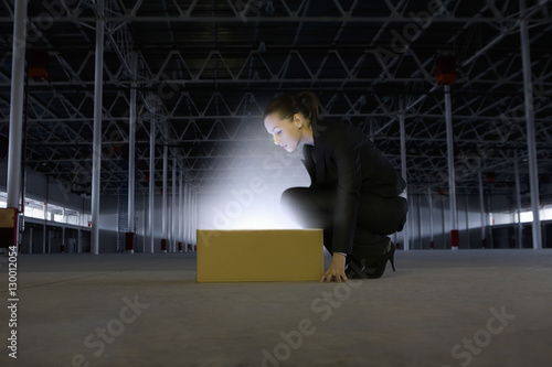 Poster Full length side view of businesswoman looking at glowing box in empty warehouse